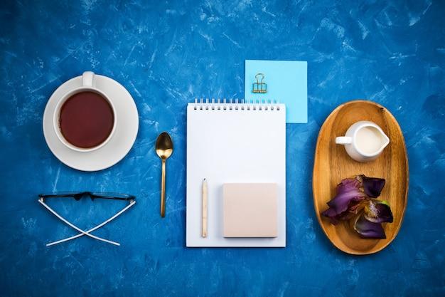 Maquette plate élégante avec une tasse de thé noir, un cahier, des verres et un crayon, un porte-lait sur un plateau en bois sur fond de ciment bleu