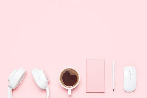 Maquette plate tendance avec écouteurs, agenda, stylo, souris sans fil et tasse de café sur un bureau de couleur rose.
