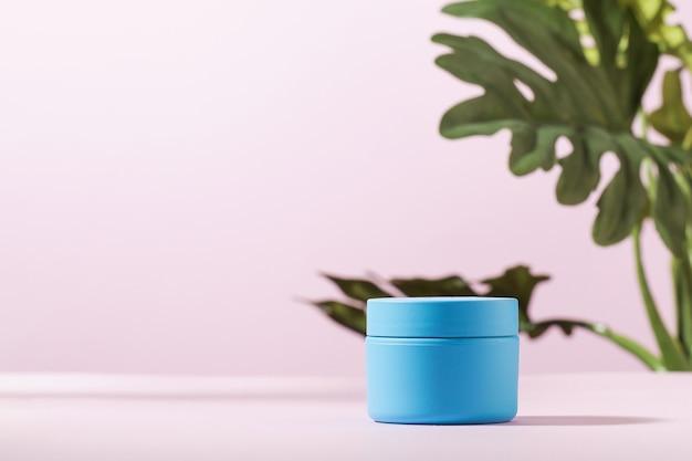 Maquette d'un pot bleu pour masque cosmétique crème sur fond rose avec un espace de copie de plante verte