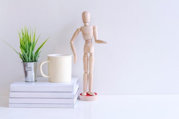 Maquette de poupée en bois, livre, tasse et plante d'intérieur sur la table blanche