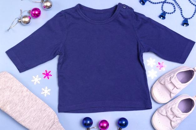 Maquette pour la conception et le placement de logos, publicité. raglan bleu pour enfants, polo, vue de dessus de chemisier, maquette sur fond bleu. rosette plate de nouvel an de vêtements de bébé