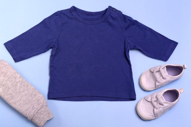 Maquette pour la conception et le placement de logos, publicité. raglan bleu pour enfants, polo, vue de dessus de chemisier, maquette sur fond bleu.