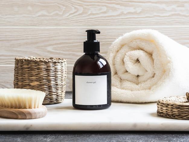 Maquette pour produits de bain dans la salle de bain, shampoing spa, gel douche, savon liquide avec une serviette à côté et divers accessoires