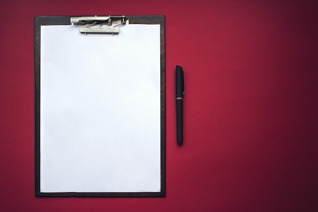 Maquette de presse-papiers en bois avec du papier blanc sur fond rouge. concept d'analyse, d'étude, de travail attentif.