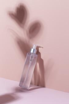 Une maquette d'un produit cosmétique sur fond rose avec des ombres tonique nettoyant pour le visage micell...