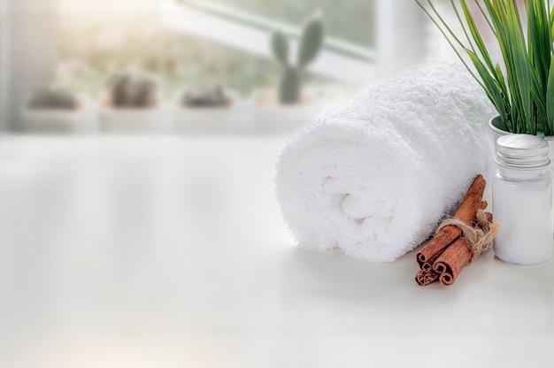 Maquette propre serviette avec une bouteille d'huile sur une table blanche près de la fenêtre.