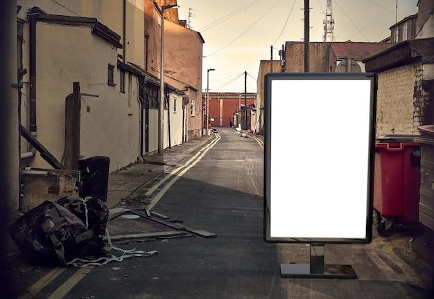 Maquette publicitaire vierge dans la rue. panneau d'affichage sur fond de ruelle sale de la ville