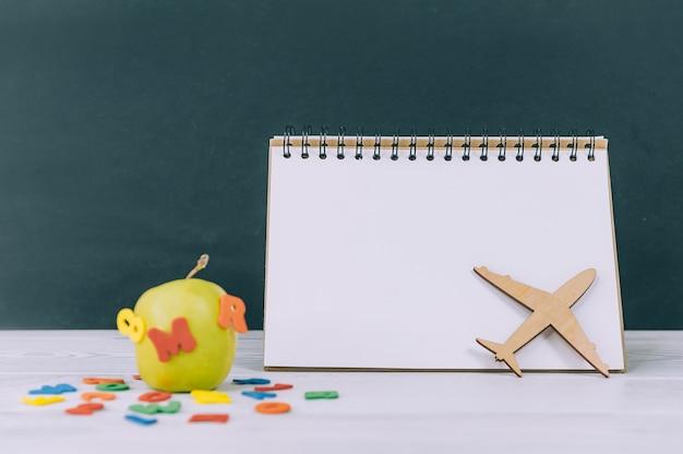 Maquette de retour à l'école. pomme verte avec lettres colorées et espace de bloc-notes.