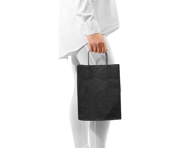 Maquette de sac en papier texturé artisanal noir blanc tenant la main