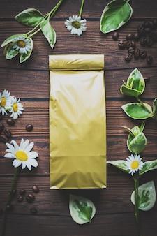 Maquette sac pochette en papier métallique doré sur une table en bois foncé allongée sur des grains de café