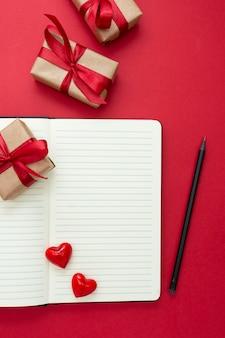 Maquette de la saint-valentin. cahier ouvert avec des coeurs rouges et des coffrets cadeaux, sur fond rouge, copiez l'espace pour le texte.