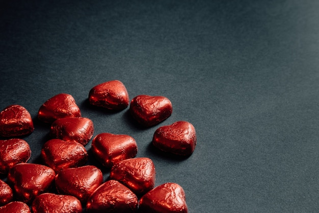 Une maquette de saint valentin avec des coeurs rouges colorés sur un fond noir foncé pour la journée de l'amour avec copie espace