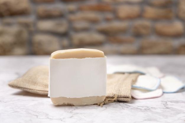 Maquette de savon fait main et tampons démaquillants réutilisables sur marbre blanc avec fond de mur en pierre