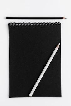 Maquette de scetchbook noir et crayons sur un espace blanc. vue de dessus, espace copie