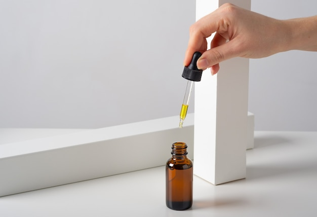 Maquette de sérum cosmétique pour le visage, bouteille en verre brun huile avec une pipette sur un fond blanc minimaliste élégant avec un décor géométrique.
