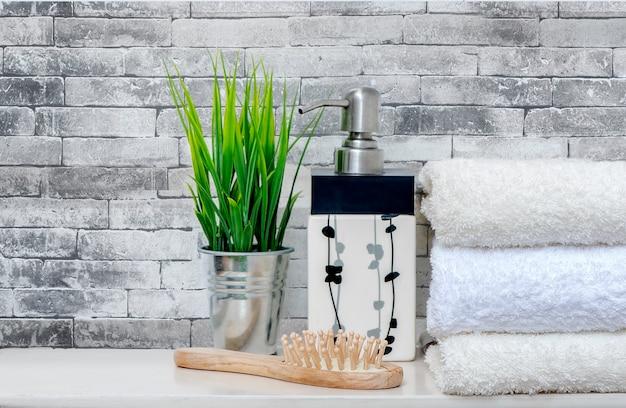 Maquette de serviettes propres avec plante d'intérieur, peigne en bois et bouteille de savon liquide sur une table blanche