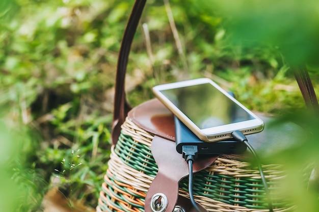 Maquette d'un smartphone avec chargeur power bank sur un panier dans la forêt. concept sur le thème des loisirs de plein air.