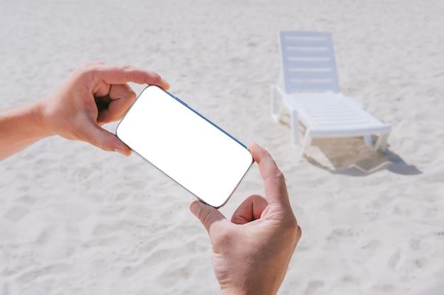 Maquette de smartphone dans des mains masculines. avec en toile de fond la plage et les transats. concept sur le thème de la détente.