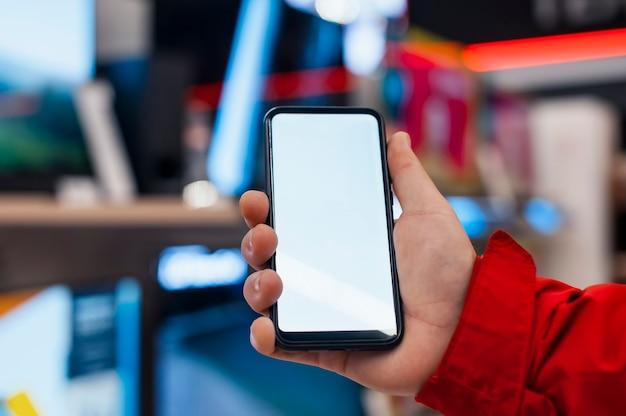 Maquette d'un smartphone avec un écran blanc entre les mains d'un homme. téléphone sur l'espace des téléviseurs dans le magasin.