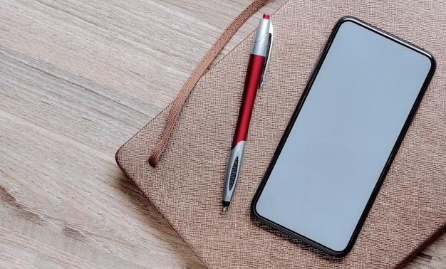 Maquette smartphone écran blanc avec stylo et agenda sur la table.