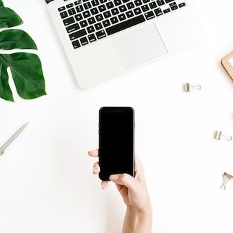 Maquette de smartphone avec écran noir dans l'espace de travail de la main féminine