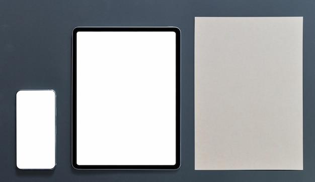 Maquette smartphone avec écran vide de tablette et papier brun sur fond noir