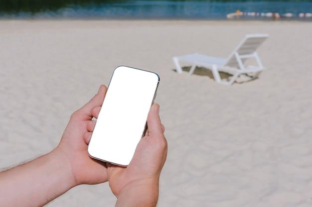 Maquette d'un smartphone entre les mains d'un homme sur la plage. sur fond de transats de sable, d'eau et d'arbres.