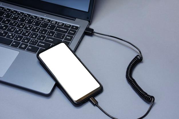 Maquette d'un smartphone avec un gros plan d'écran blanc en cours de chargement à partir d'un ordinateur portable sur le fond d'un tableau gris.