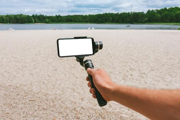 Maquette d'un smartphone avec un stabilisateur d'appareil photo dans la main d'un homme. sur fond de plage de sable et de nature avec un lac.
