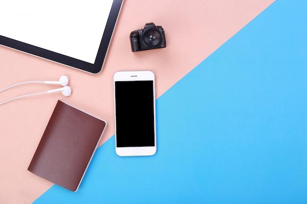 Maquette smartphone vue de dessus avec tablette et passeport sur fond pastel rose et bleu