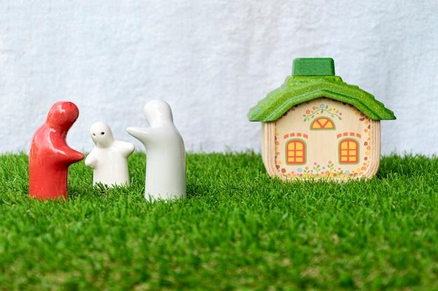 Maquette de la statue de la famille et de la maison sur le sol en herbe avec un fond blanc