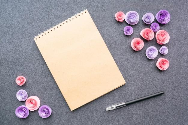 Maquette avec un stylo cahier vide et des roses roses en papier