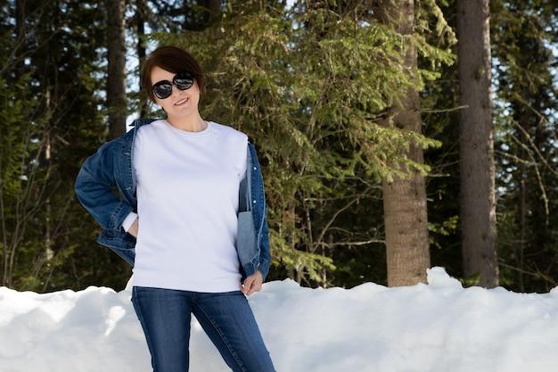 Maquette de sweat-shirt à col rond en molleton blanc avec une femme portant des lunettes de soleil par un bois enneigé. modèle de sweat-shirt épais