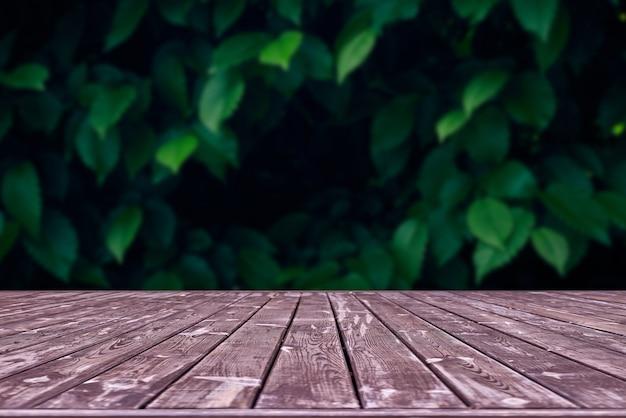 Maquette. table de terrasse en bois vide avec espace de bokeh de feuillage.