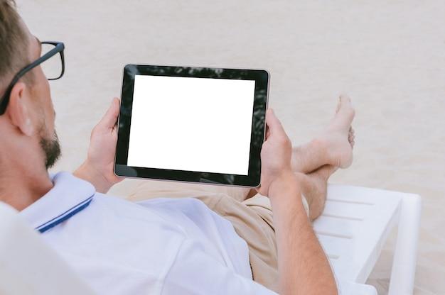 Maquette tablette dans les mains d'un homme d'affaires allongé sur une chaise longue sur la plage. sur fond de sable. concept sur le thème de la détente.