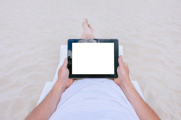 Maquette tablette dans les mains d'un homme allongé sur une chaise longue sur la plage. sur fond de sable.