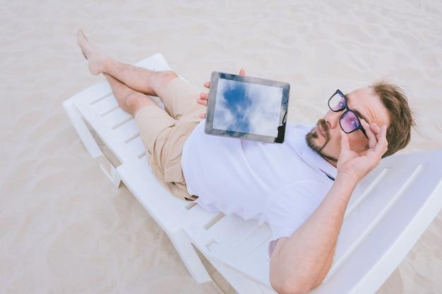 Maquette tablette dans les mains d'un homme avec des lunettes regardant la caméra et allongé sur la plage sur une chaise longue. sur fond de sable.
