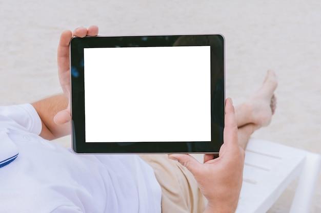 Maquette d'une tablette entre les mains d'un blogueur allongé sur une chaise longue sur la plage. sur fond de sable. notion de voyage.