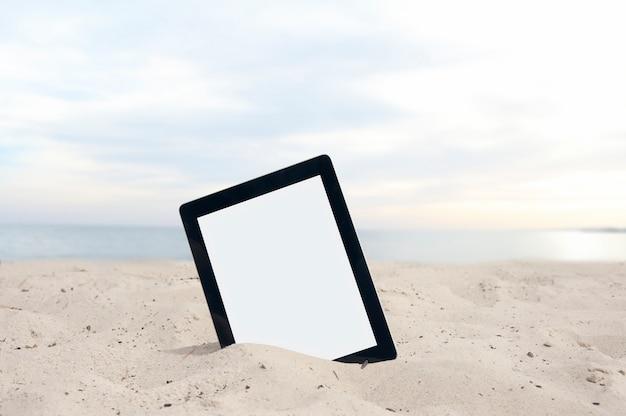 Maquette tablette avec gros plan écran blanc sur la plage sur le fond de la mer avec des vagues et le ciel avec des nuages.