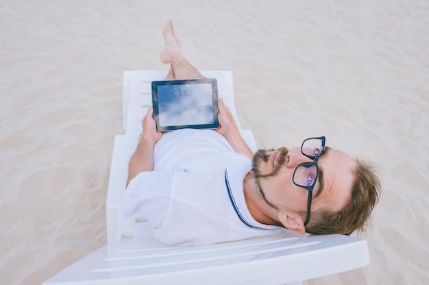 Une maquette d'une tablette noire entre les mains d'un homme avec des lunettes, allongé sur une chaise de plage. sur fond de sable.