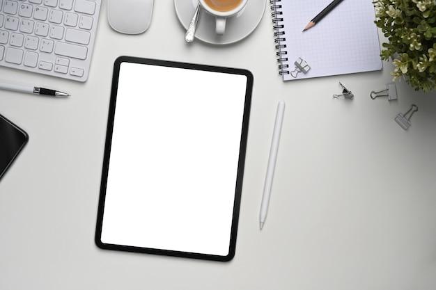 Maquette de tablette numérique avec écran blanc, plantes et fournitures de bureau sur un bureau blanc.