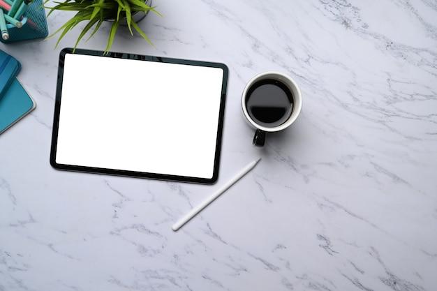 Maquette de tablette numérique avec écran vide, stylet, tasse à café et espace de copie sur une table en marbre.