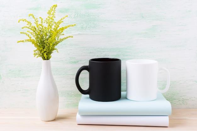 Maquette de tasse blanche et noire avec de l'herbe à fleurs vertes ornementales