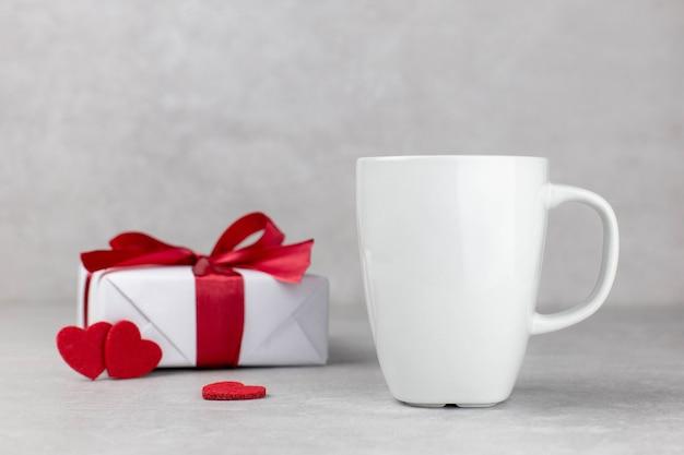 Maquette de tasse blanche vierge avec boîte-cadeau et coeurs rouges, pierre de béton léger.