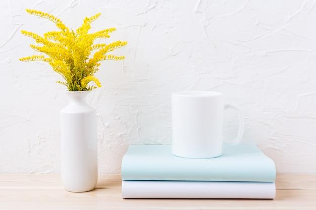 Maquette de tasse de café blanc avec de l'herbe à fleurs jaunes ornementales