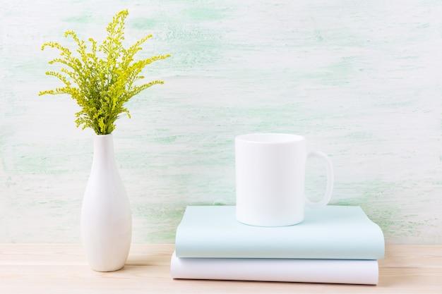 Maquette de tasse de café blanc avec de l'herbe à fleurs vertes ornementales