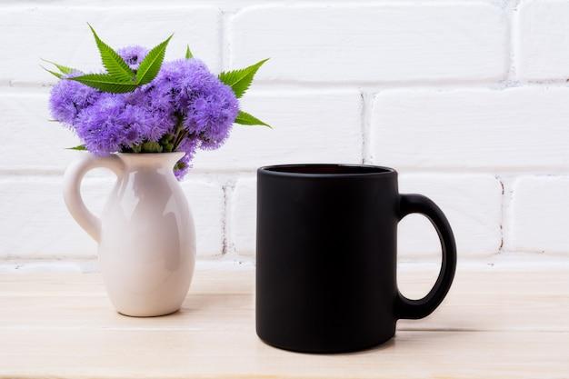 Maquette de tasse de café noir avec ageratum bleu dans un pichet