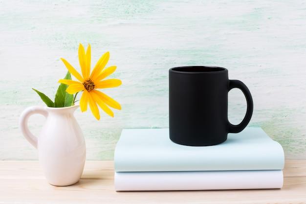 Maquette de tasse de café noir avec des fleurs de rosarin jaune dans un pichet