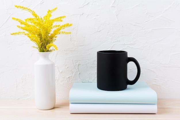 Maquette de tasse de café noir avec de l'herbe dorée ornementale et des livres