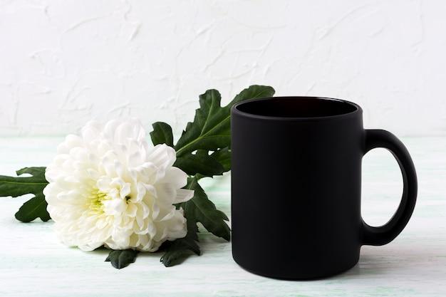 Maquette de tasse à café noire avec chrysanthème blanc